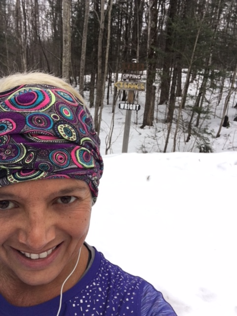 Image description: Head shot of Tracy, smiling, wearing a pink, blue, purple and yellow buff, white ear buds, and a purple shirt with white specks, snow and trees in the background, and a sign post with surnames on it indicating the people who live in the lane.