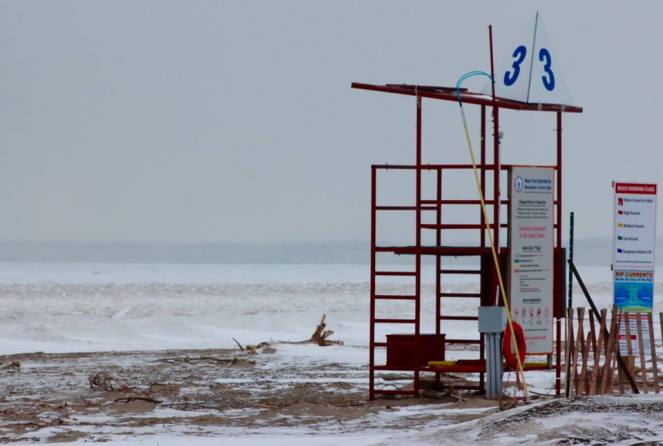 Image description: Red lifeguard stand with the number 3 on it, with some rescue equipment on a snow-covered beach.