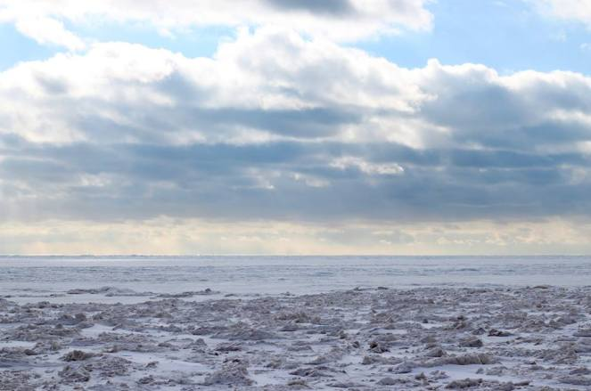 Image description: Lake frozen in brown and white uneven crests in the foreground, then leveling off to a white expanse towards the horizon, and a blue sky with clouds.