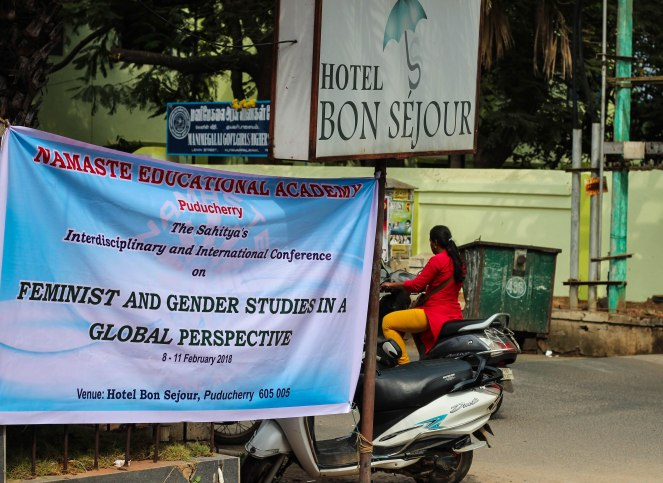"Image description: Blue banner sign that says ""Namaste Educational Academy, Puducherry"" in red lettering, followed by ""The Sahitya's Interdisciplinary and International Conference"" in purple lettering, followed by ""on FEMINIST AND GENDER STUDIES IN A GLOBAL PERSPECTIVE, 8-11 February 2018"" in black lettering. ""Venue: Hotel Bon Sejour, Puducherry 605 008"" in black lettering."
