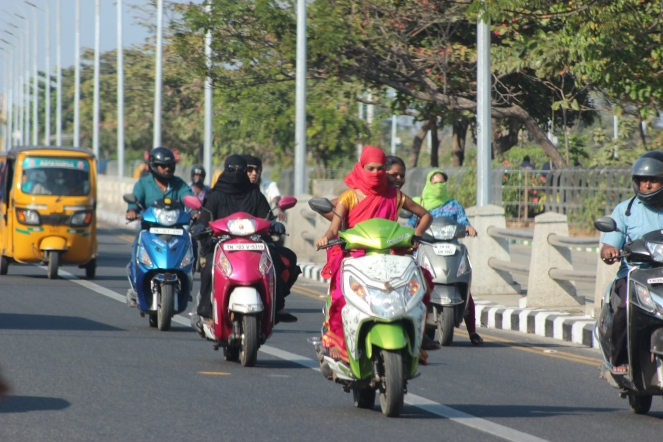 Image description: street scene dominated by three women on scooter style motorbikes. The one in front is on a lime green bike wearing a red sari and headscarf, with a smiling woman peeking over her shoulder from behind her. Next is a woman on a pink bike in a full black burka, and a woman on a silver bike in a green head scarf. Men on two other bikes are looking at the women. A yellow auto-rickshaw is pulling up the rear. Street light posts and trees line the side of the road.