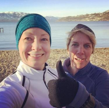 Image description: Alison Conway (right) and Karis Shearer (left) dressed for outdoor running, with light jackets and hats, outside on a beach with water and mountains behind them. Alison is giving a 'thumbs' up and both are smiling as they look directly into the camera for what is clearly a selfie.