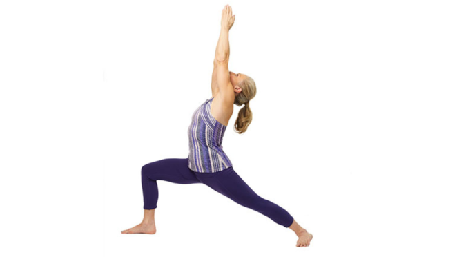 A woman in a warrior lunge pose, front knee bent, back leg straight, with torso upright and arms straight and overhead.