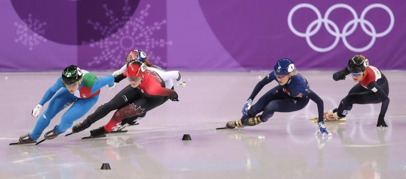 Olympic women's 500-meter short track speed skaters in motion.