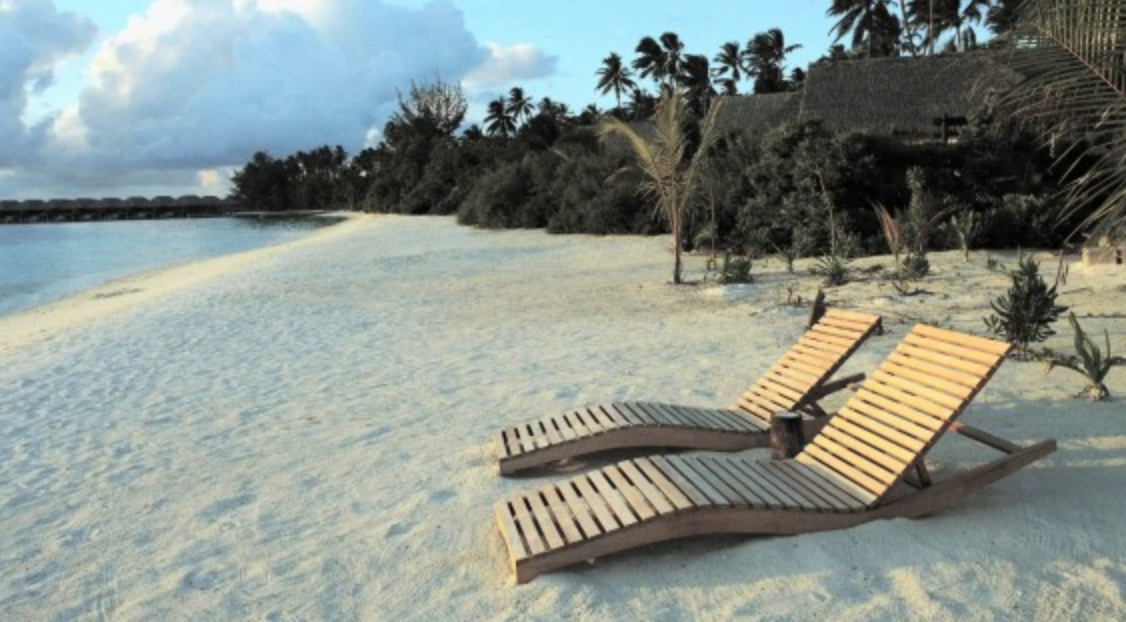 Two wooden chaise lounges on a white sandy beach.