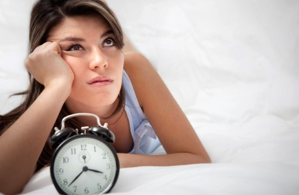 A woman looking impatient, lying propped up on a bed next to an alarm clock.