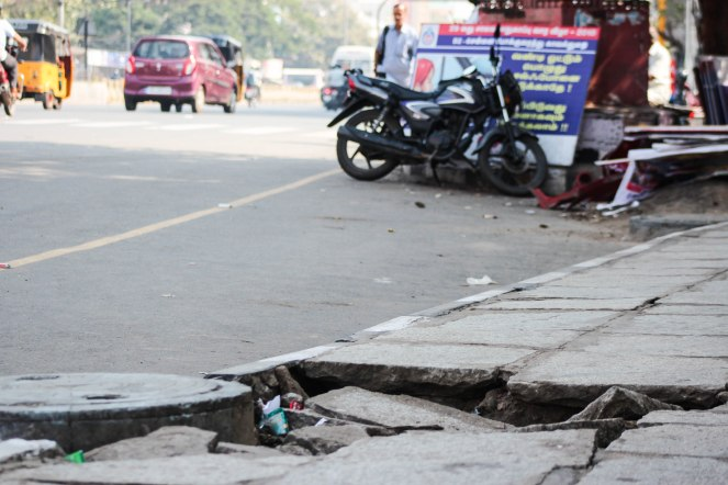 Image description: ground level angle showing a big hole in the sidewalk, beyond that is the road with a car and motorcycle and yellow auto-rickshaw, and and a parked motorcycle.