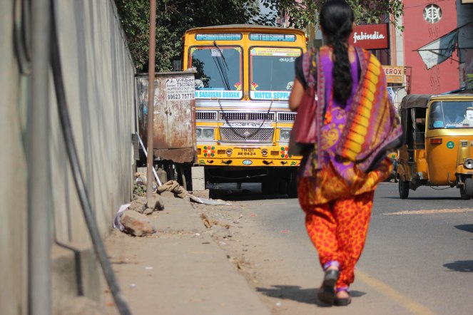 Image description: woman in bright colours walking on the road, away from the direction of the camera towards a yellow truck. The sidewalk on her left is totally blocked by debris and a rusted trailer.