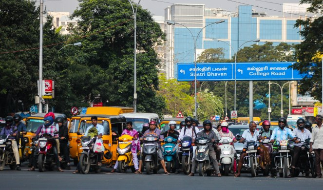 Image description: A crowd of motorcycles, yellow auto-rickshaws, and cars wait in a pack at a busy intersection in Chennai for the light to turn green. In the background: green leafy trees on the right, street lights and a blue road sign above the road that says Sastri Bhavan (pointing left) and College Road (pointing right) and the same in Tamil script, a tall building with blue reflective windows in the distance.