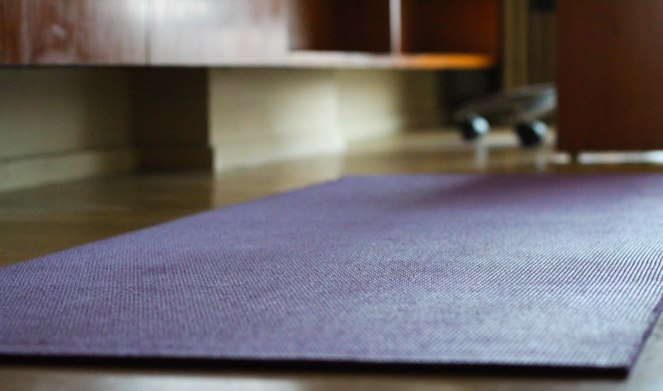 Image descrription: purple yoga mat on the floor in Tracy's hotel room, with wood shelving and desk in the background.