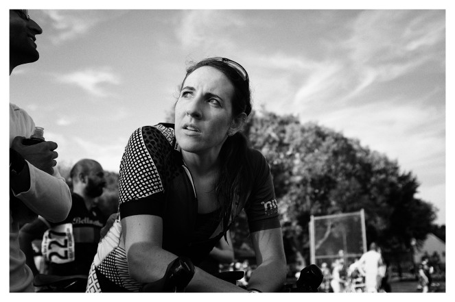 Erin, a dark haired woman with her hair pulled back, looks onto another spectator while wearing her cycling kit after one of her first cyclocross races. She is leaning forward on her bike. Her sunglasses are resting on top of her head, her jersey is zipped down, and her hair is wet from sweat. Photo Credit: Carlos Sabillon