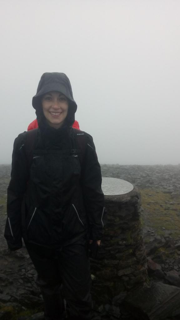 Bettina, looking distinctly wet but happy, in hiking gear at the summit of Skiddaw in the Lake District, UK