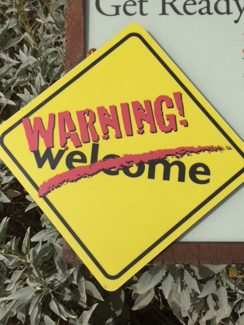 "yellow sign saying ""warning!"" and ""welcome"" (with a red line through it)"