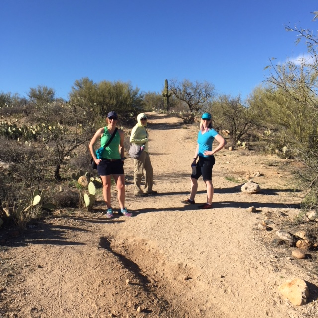 Steph, Janet, and Kathy, hands on hips, waiting on the trail for me.