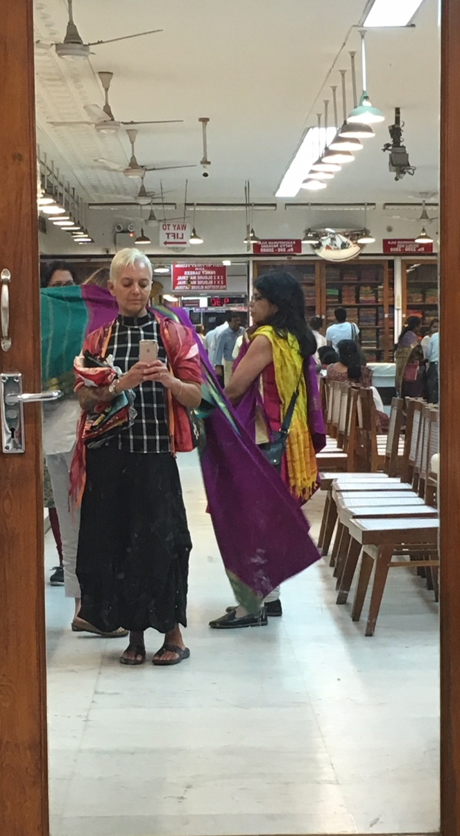 Image description: Smart phone shot in Nalli's sari shop in Chennai, India. Tracy in a long skirt and check top taking a phone pic in the mirror with Nandi on the right (in the mirror) looking at a sari, the mirror frame visible.