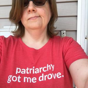 The author, a white woman in her mid forties, wearing sunglasses and a red tshirt that reads 'patriarchy got me drove' Grey siding is visible in the background.