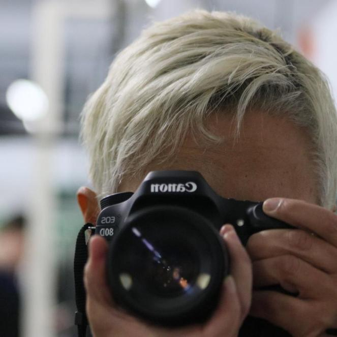 Image description: head shot of tracy, short blond hair, looking through the viewfinder of a Canon EOS 80D, words reversed because of the mirror image, finger on the shutter release.
