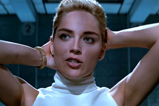 Image description: Sharon Stone in Basic Instinct (1992). Upper body shot with short blond hair, hands behind head, and a white sleeveless turtleneck, mouth slightly open as if speaking.