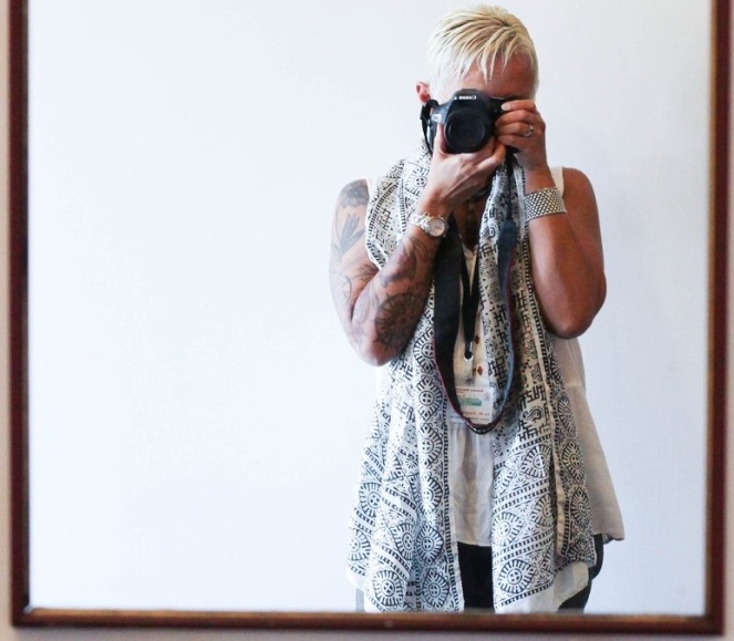 Image description: Mirror shot of Tracy from the thighs up, looking through camera viewfinder, wearing a flowing patterned silk scarf, and a sleeveless blouse, a watch on tattooed left arm and silver bracelet on right arm. Plain background.