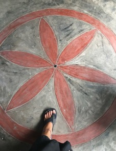 Image description: Tracy's left foot in a sandal on a floor with a simple painting of a six-petaled red flower in a red circle.