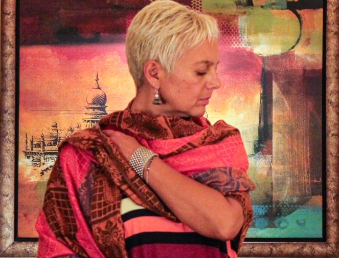 Image description: Tracy, short blond hair, head turned to the side and looking down, arm slung across body to hold up a colourful pashmina, against the background of a colourful framed painting.