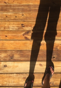 Image description: Tracy's right foot in a sandal in lower right corner of frame and her shadow from thighs down against a wood plank floor.