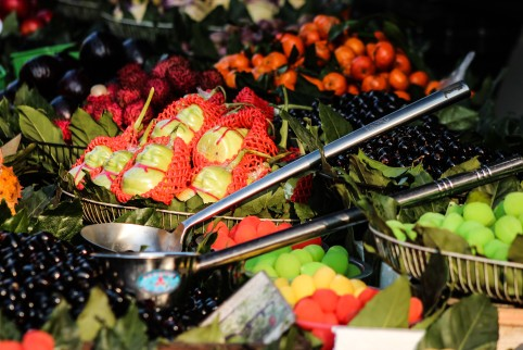 Image description: market stall in Suzhou of varieties of fresh fruit in metal baskets with two large metal scoops.