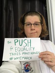 The author, a white woman in your mid-forties with dark blonde hair, is wearing a martial arts uniform and holding a sign that says 'the push for equality takes many hands #WhyIMarch' She is wearing glasses. The background is grey cloth.