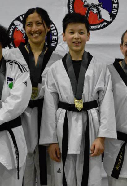 A woman and a slightly shorter boy, both smiling, in taekwondo uniforms with black belts and gold medals around their necks. Other people's shoulders are visible in the picture.