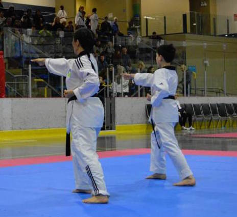 a woman and boy, both in taekwondo uniforms, side by side in a front stance executing a hand technique