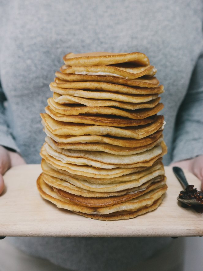 Photo by Brigitte Tohm on Unsplash. Image description: A giant stack of plain pancakes on a wooden cutting board.
