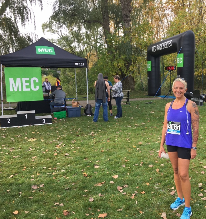 Image description: (MEC 10K in October 2017) Tracy standing in the right foreground in running shorts, tank, and shoes with a race bib 2065. Canopy with MEC sign hanging from it in the left background, and a race podium (1-2-3), and a finish line inflatable arch, and a few people in the background. Green grass, fall leaves, trees.