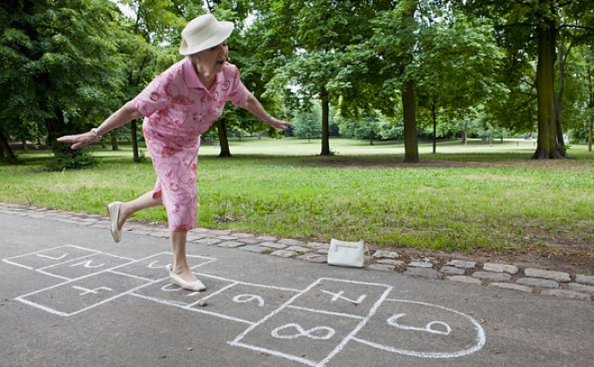 Woman in a pink outfit and white hat playing hopscotch in a park. And it doesn't look cold at all.