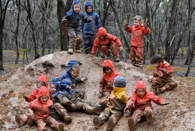 A big pile of muddy, raingear-clad, happy kids, sliding down a muddy mound.