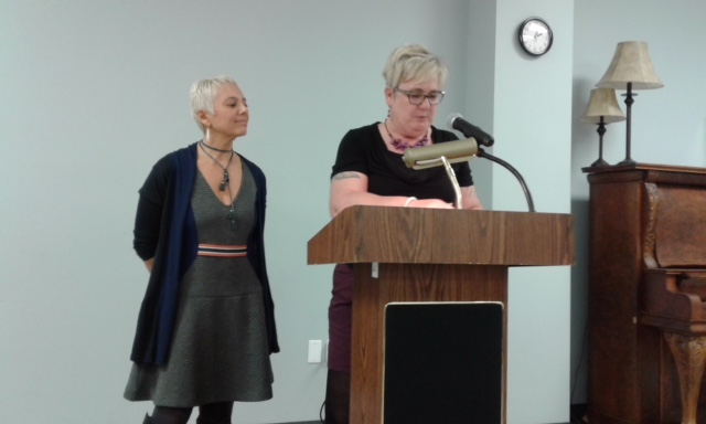 Image description: Tracy on left looking at Sam at the podium, reading.