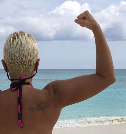 Image description: Upper body back shot of Tracy, short blond hair in a striped halter bikini top, flexing her right bicep, facing towards a turquoise sea, light surf and partly cloudy sky.