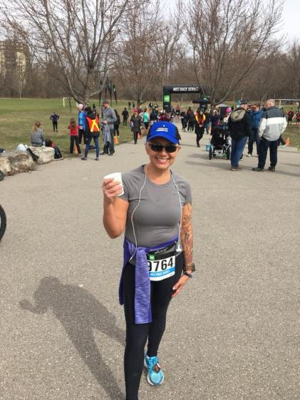 Image description: Tracy in running tights, a t-shirt, ballcap and sunglasses, long-sleeved run top around waist, race bib on front, smiling and holding a paper cup in her right hand, people, grass, trees, and inflatable race arch in background.