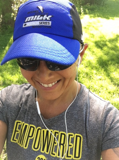 "Image description: Upper body selfie of Tracy in ball cap, sunglasses, earbuds, and a t-shirt that says ""EMPOWERED"" on it, smiling, grass and sunlight in the background. [She is running in Springbank Park, along the river]"