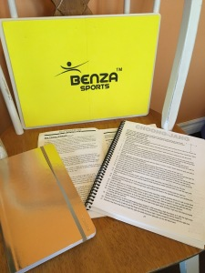 The author's tools for preparing for her test - a yellow rectangular plastic board for kicking, a gold notebook for recording her progress, and two white books printed with black type that include training theory and lists of patterns.