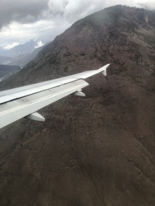 The wing of a plane seems to brush against a small mountain as it lands