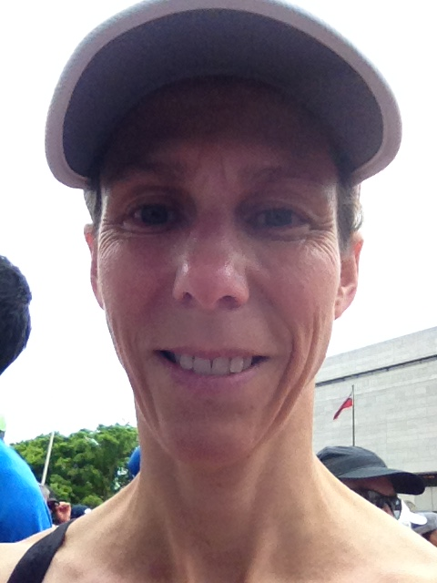 Image description: Head shot of Jennifer smiling, wearing a visor, pre-race, trees, people, building, flag and white sky in background.