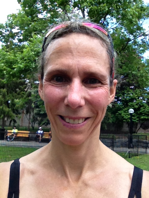 Image description: Headshot of Jennifer, post-race, smiling, sunglasses on head, trees and park benches in background.