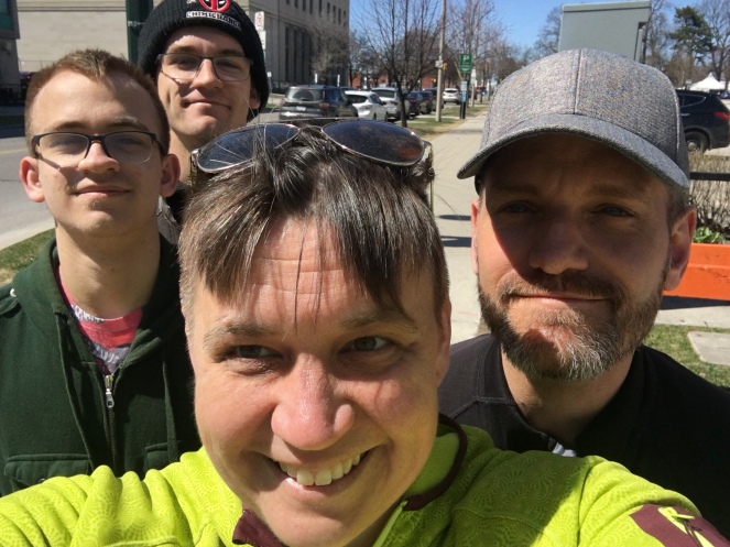 Four smiling humans gather in for a sidewalk selfie on a warm sunny day
