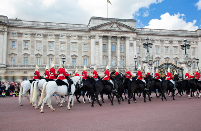 The changing of the Queen's guard at Buckingam palace, with red uniformed guards on horseback.