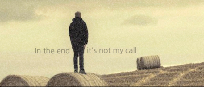 "A person standing in a field on a haybale, with the words ""in the end it's not my call""."