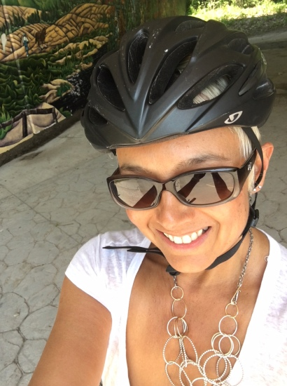 Image description: Selfie of Tracy in bike helmet, work top, necklace and sunglasses, smiling. Background: partial wall mural and sunny green space.