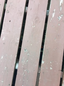 Three weathered brown deck boards. There are finger-width spaces between each one.