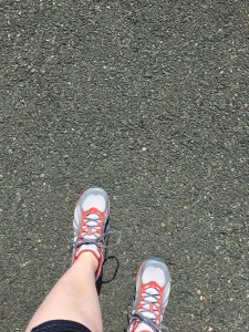 The author's feet in her new grey and pink sneakers. She is standing on black asphalt.