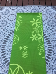 A green yoga mat with flowers printed on it in yellow rests on a larger beige patio mat that has circular patters on it.