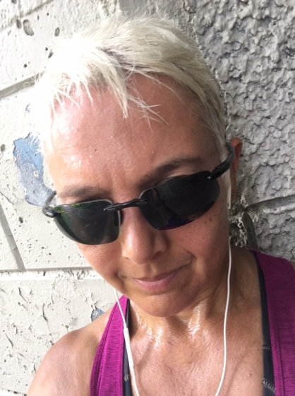 Image description: Head shot of Tracy, short blond hair, sunglasses, earbuds, sweating, leaning up against a white brick wall. Not smiling.
